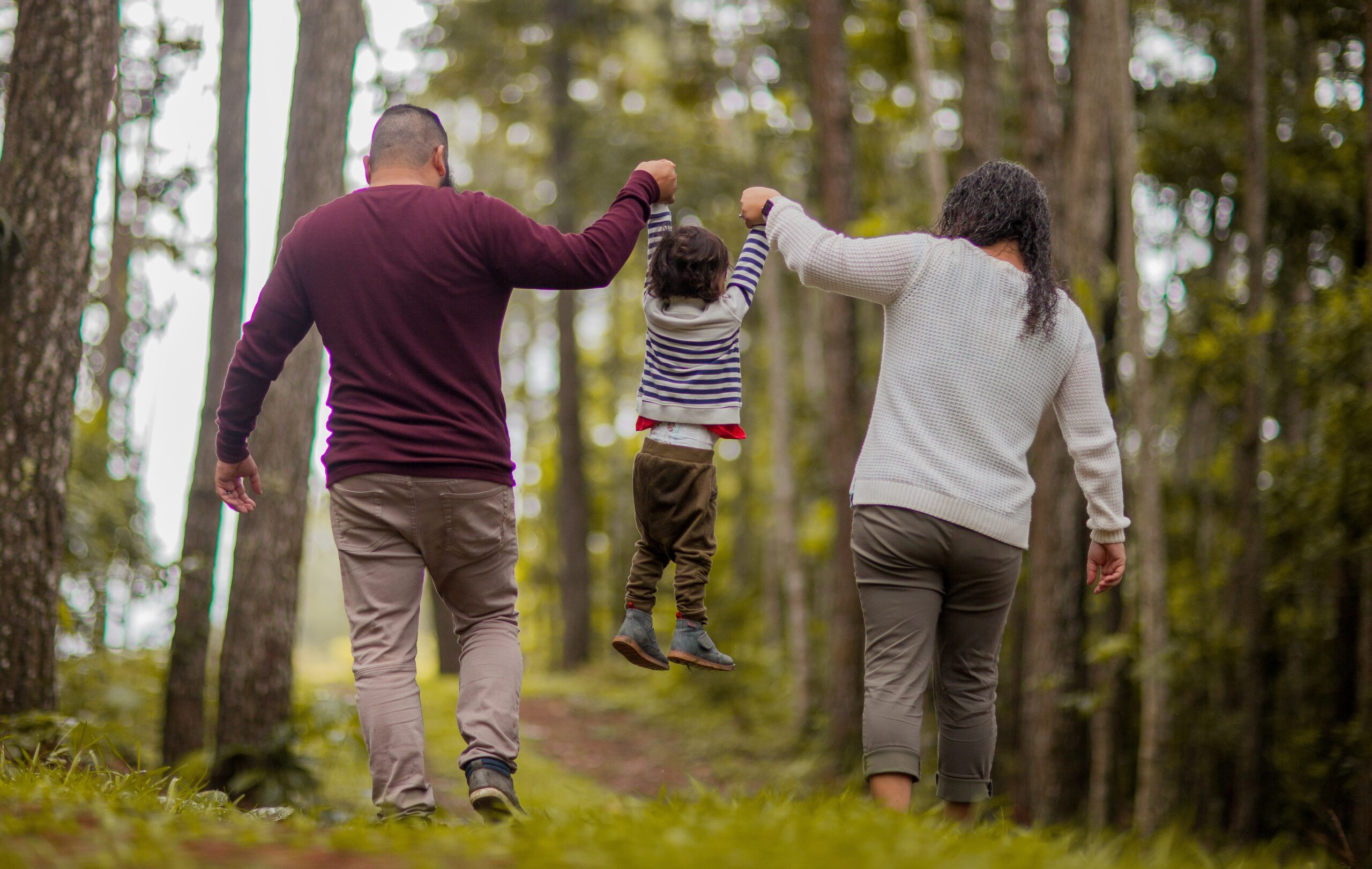 two adults and a young child walking in a forest while holding hands - sound walk